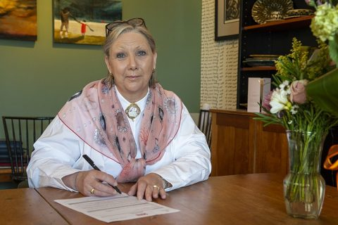 Dianne Taylor-Gearing sitting in her office signing the Dimensions Charter