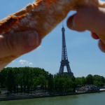 A baguette being broken with the Eiffel Tower in the background.