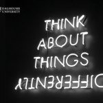 """neon lights write out the words """"think about things differently"""" on a black background. Both the NSCAD and Dalhousie logos are in the top left corner of the image."""
